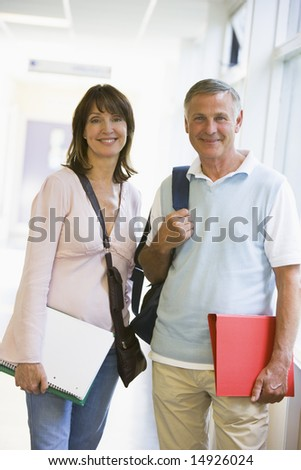 A man and woman with backpacks standing in a campus corridor - stock photo