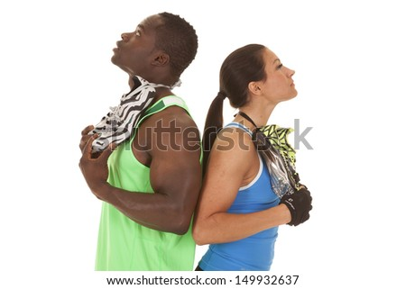 A man and woman with running shoes over their shoulders looking up. - stock photo