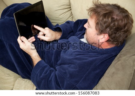 A man at home on his couch using this tablet PC.   - stock photo