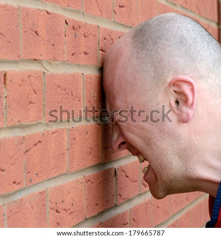 a man banging his head against the wall in frustration - stock photo