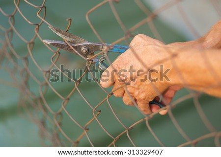 A man breaking down the fence with cutter. Immigration concept - stock photo