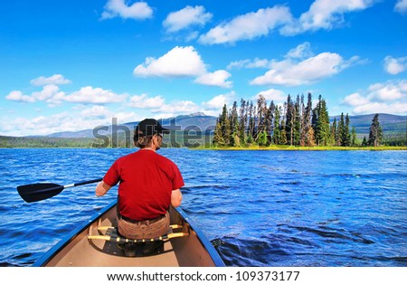 A man canoeing on a lake in the wilderness of British Columbia, Canada - stock photo