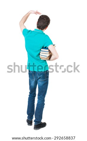 A man carries a heavy pile of books and waves . back view. Rear view people collection.  backside view of person.   Man holding a heavy stack of books under his right arm and waving a hand in greeting - stock photo