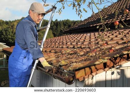 A Man Cleaning a rain gutter on a ladder - stock photo