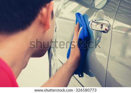 A man cleaning car with microfiber cloth - stock photo