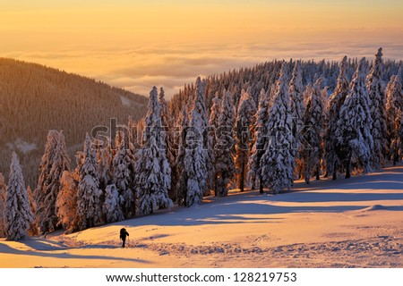 A man climbing up the snowy hill, inversion cloud in the background - stock photo
