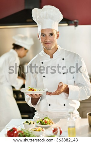A man cook chef is standing in a professional kitchen presenting a plateful with fine food. He is looking at camera, wearing white chef clothes and hat. Shot with blurred background. - stock photo
