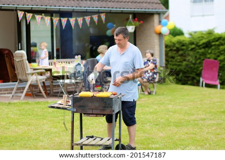 A man cooking meat on barbecue for summer family dinner at the backyard of the house - stock photo