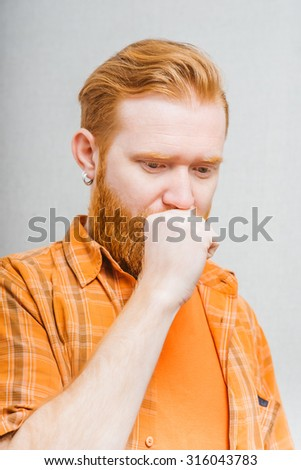 A man coughing into his fist. Gray background - stock photo