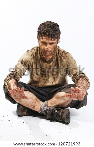 A man covered in mud sitting on the floor, trying to survive - stock photo
