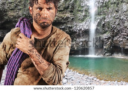 A man covered in mud with a rope, trying to survive, with a green lake in the background - stock photo