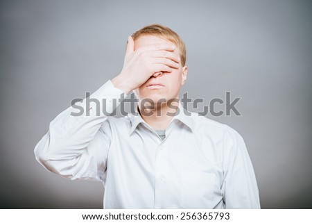 A man covering his eyes with his hands - stock photo
