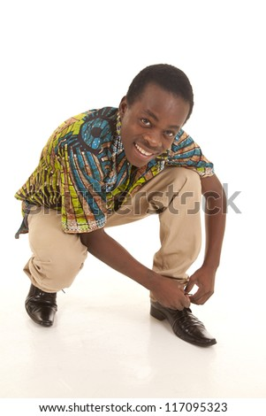 A man crouching down to tie his shoe with a smile on his lips - stock photo
