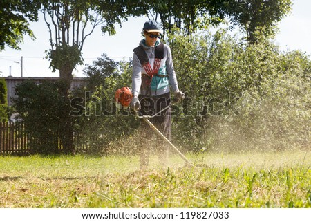 a man cut the grass with a lawn trimmer - stock photo