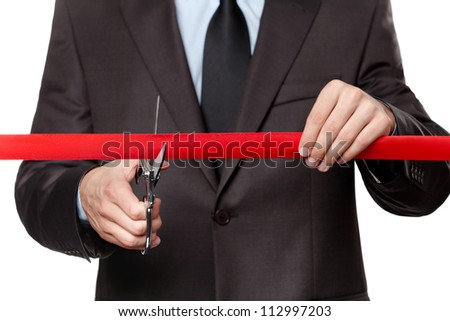 A man cutting a scarlet satin ribbon with scissors, isolated on white - stock photo