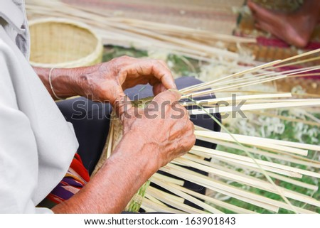 A man demonstrations use of bamboo woven by hand. - stock photo