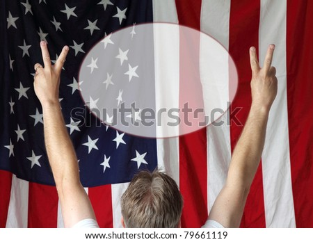 A man displays the peace sign toward the American flag - stock photo