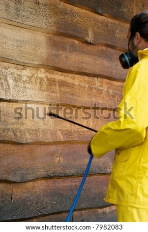 a man doing a chemical wash on the side of a garage - stock photo