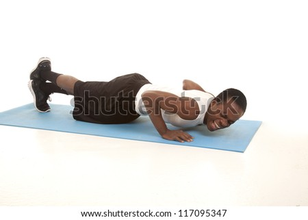 A man doing a push up with a painful expression on his face. - stock photo