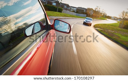 A man driving a red car towards a bend in the road. - stock photo