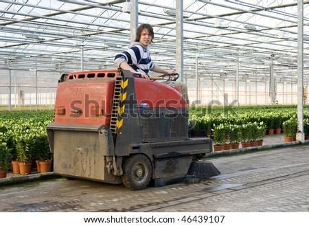 A man, driving an industrial cleaning cart, working hiw way through the concrete flooring of a huge glasshouse - stock photo