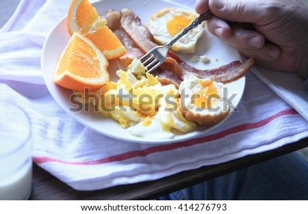 A man eats a hearty breakfast of bacon, scrambled eggs, biscuit with jam and orange sections. - stock photo