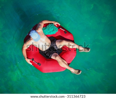 a man floating down a river in a blow up tube with a baseball cap on and shorts on a hot summer day from overhead  - stock photo