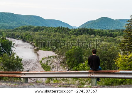 A man gazing out to the hills and mountains in Cape Breton  - stock photo