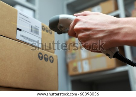A man gets on the hip scaner in operations directed on printed barcode. Warehouse scene. Shallow DOF! - stock photo