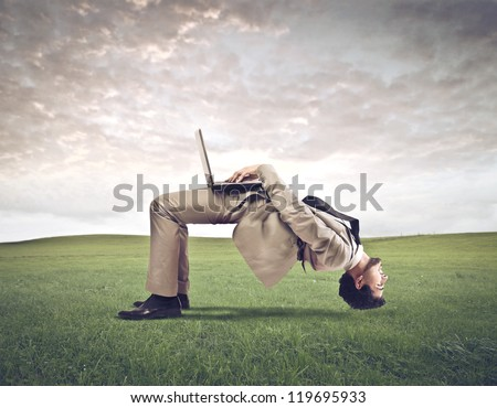 A man gets upside down while using a computer in a large field - stock photo