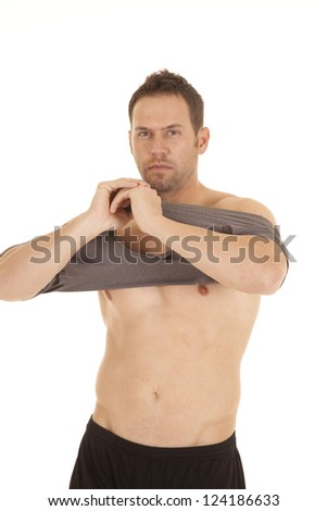 A man getting ready to put his shirt on after not having one on - stock photo