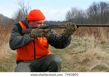 A man getting ready to shoot his gun while hunting - stock photo