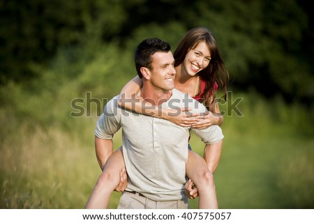 A man giving his girlfriend a piggyback - stock photo