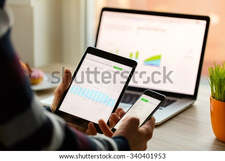 A man hand holding screen Apple app showing on IPad mini in office. Apple is the most valuable technology company in the World. PRAGUE, CZECH REPUBLIC - NOVEMBER 17,2015 - stock photo