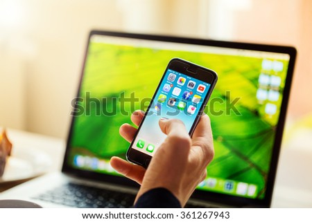 A man hand holding screen Apple app showing on IPhone 6 in office. Apple is the most valuable technology company in the World. PRAGUE, CZECH REPUBLIC - NOVEMBER 17,2015 - stock photo