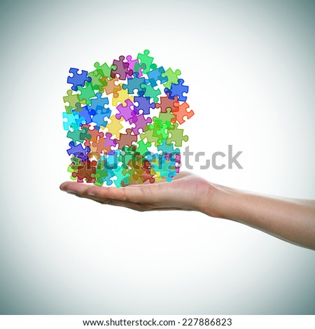 a man hand with a pile of puzzle pieces of different colors as the symbol for the autism awareness - stock photo