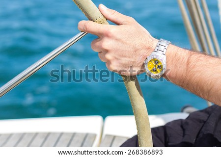 A man hand with a watch holding a sailing vessel wheel - stock photo