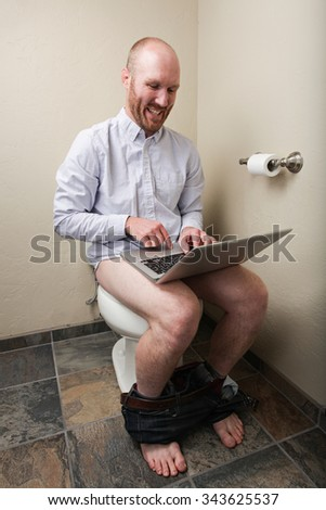 A man happily on his computer while on the toilet - stock photo