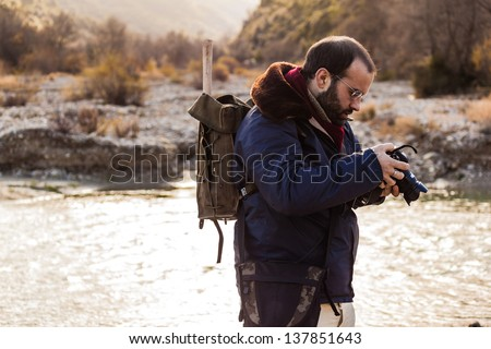 a man hiking and looking at the screen of a digital single lens reflex - stock photo