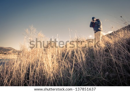 a man hiking and shooting with a digital single lens reflex - stock photo