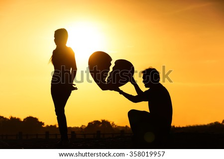 A man holding a big broken heart and an angry woman / difficult love and relationship concept / one sided love concept - stock photo