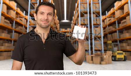 A man holding a blank paper in a distribution warehouse, ideal for inserting your own message - stock photo