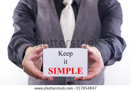 A Man holding a business card with the words, keep it simple, written on it. - stock photo