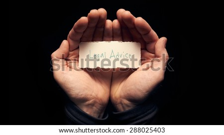 A man holding a card in cupped hands with a hand written message on it, Legal Advice. - stock photo