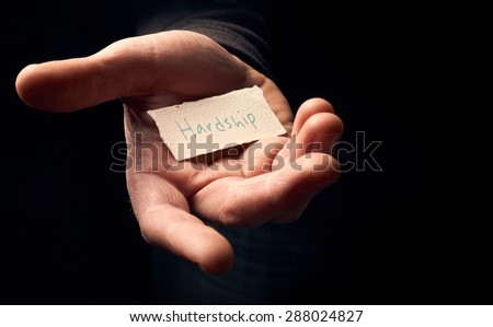 A man holding a card with a hand written message on it, Hardship. - stock photo