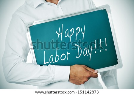 a man holding a chalkboard with the sentence happy labor day written in it - stock photo