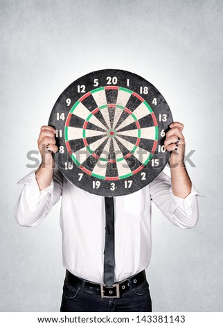 A man holding a dartboard over the head - stock photo