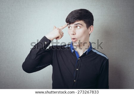 A man holding a finger to his temple, he thinks. On a gray background. - stock photo