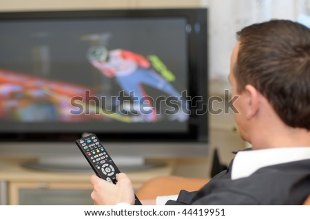 A man holding a remote control while watching a ski jumping on TV. - stock photo