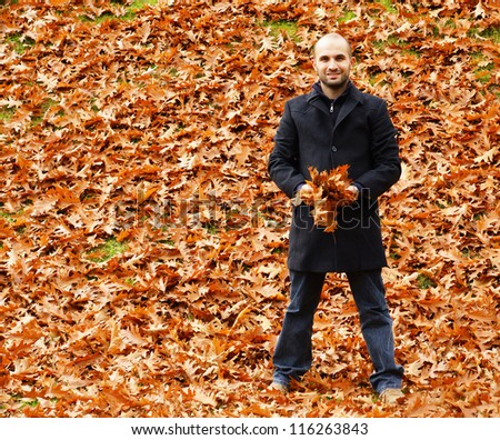 A man holding leaves at the park - stock photo